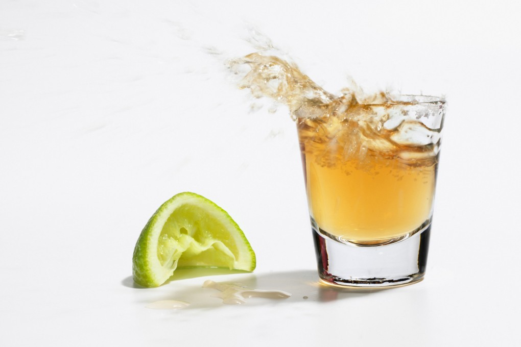 Close up of tequila splashing out of glass