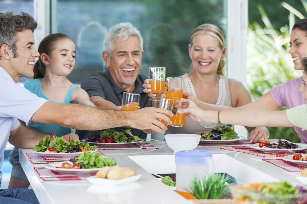 big generation family, parents, children and grandparents, drink orange juice toast happy smile lunch dinner at table, home