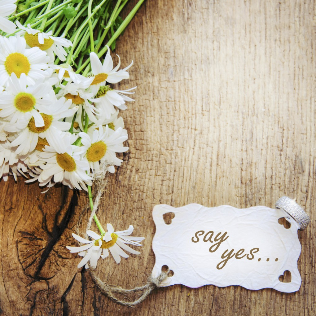 Beautiful bouquet of chamomile on vintage wooden table.